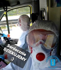 Zdjęcie przedstawia ratowników medycznych w ambulansie jadących do zdarzenia ubranych w kombinezony ochronne.